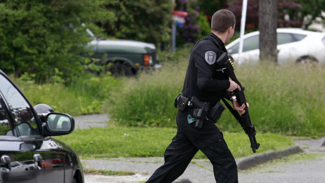 A police officer runs across a street in the University district in Seattle close to where a gunman killed two people and critically wounded three others at a cafe Wednesday, May 30, 2012. Not long after a gunman opened fire at the cafe in the north Seattle neighborhood, a woman was shot to death in downtown Seattle and her car taken and later abandoned in Seattle's West Seattle neighborhood. It was not immediately clear if the incidents were connected. (AP Photo/Elaine Thompson)