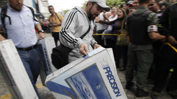Shoppers carry television sets after purchasing them at Daka a appliance store in Caracas, Venezuela, Saturday, Nov. 9, 2013. In a bid to bring down prices that have jumped in tandem with demand for dollars on the black market, Venezuela's President Nicolas Maduro on Wednesday tightened controls on currency transactions. With hard-fought municipal elections approaching next month, he also ordered the military to shut down businesses found hoarding products or speculating on prices. (AP Photo/Ariana Cubillos)