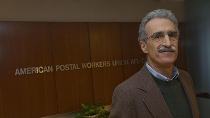 """Mark Dimondstein, president of the American Postal Workers Union poses for a photo at their Washington headquarters, Friday, Jan. 17, 2014. The opening of Postal Service retail centers in dozens of Staples stores around the country is being met with threats of protests and boycotts by the agency's unions. The new outlets are staffed by Staples employees, not postal workers, and labor officials say that move replaces good-paying union jobs with low-wage, nonunion workers. """"It's a direct assault on our jobs and on public postal services,"""" said Mark Dimondstein, president of the 200,000-member American Postal Workers Union. (AP Photo/Pablo Martinez Monsivais)"""