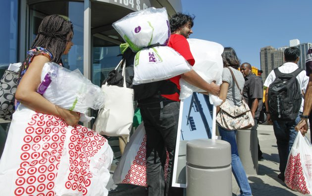 In this Wednesday, Aug. 22, 2012, photo, shoppers carry their purchases at a Target in Chicago. The Commerce Department said Friday, Sept. 14, 2012, that U.S. retail sales rose in August from July because consumers paid higher gas prices and bought more cars and trucks. They were more cautious elsewhere, suggesting the weak economy has made many selective about spending. (AP Photo/Sitthixay Ditthavong)