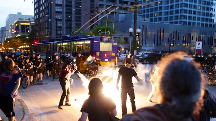 "Police face off against demonstrators during a May Day protest in Seattle Wednesday, May 1, 2013. Police used ""flash bangs"" and pepper spray against some protesters who pelted them with rocks and bottles late Wednesday, as violence erupted during May Day in Seattle. Several dozen protesters, many using bandanas to cover their faces, began clashing with police in downtown Seattle hours after a peaceful immigrant-rights march ended. (AP Photo/Jordan Stead, seattlepi.com)"