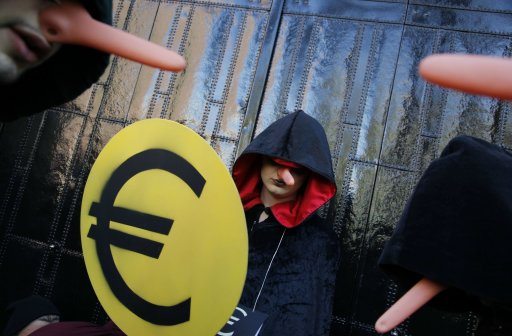 Hooded protestors with Pinocchio-type noses, one holding a Euro sign, walk up to the gate of the NYSE Euronext stock exchange in Amsterdam, Netherlands, Saturday Oct. 15, 2011, during a demonstration in support of the Occupy Wall Street movement.  Demonstrators in hundreds of cities all over the world are protesting against what they call the corporate power and the banking system. (AP Photo/Peter Dejong)
