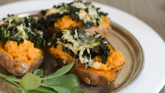 In this image taken on Dec. 3, 2012, loaded sweet potatoes with roasted garlic are shown served on a plate in Concord, N.H. (AP Photo/Matthew Mead)