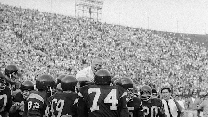 FILE - In this Nov. 28, 1964, file photo, Southern California head coach John McKay, center, is carried off the field by players after their 20-17 win over Notre Dame in an NCAA college football game in Los Angeles. Southern California rallied from a 17-0 halftime deficit, culminating with a 15-yard touchdown pass from Craig Fertig to Rod Sherman with 1:33 left. The Associated Press takes a look at some of the memorable games in college football's greatest intersectional rivalry in anticipation of Southern California hosting No. 1 Notre Dame on Saturday, Nov. 24, 2012. (AP Photo/David F. Smith, File)
