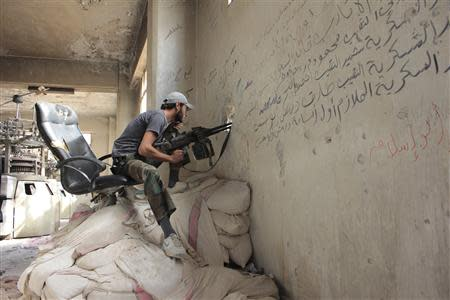 A Free Syrian Army fighter sits at a shooting position in the al-Khalidiya neighbourhood of Aleppo