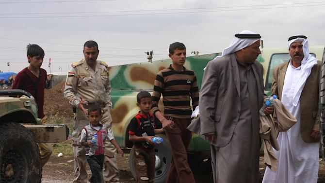 In this photo taken on Monday, April 22, 2013, Iraqi army soldiers escort young and elderly people leaving a protest site in Hawija, 150 miles (240 kilometers) north of Baghdad, Iraq. Iraqi security forces backed by helicopters raided a Sunni protest camp before dawn Tuesday, prompting clashes that killed scores of people in the area and significantly intensified Sunni anger against the Shiite-led government. (AP Photo)