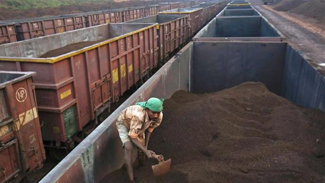 File photo of a worker levelling the iron ore in a freight train at a railway station at Chitradurga in Karnataka