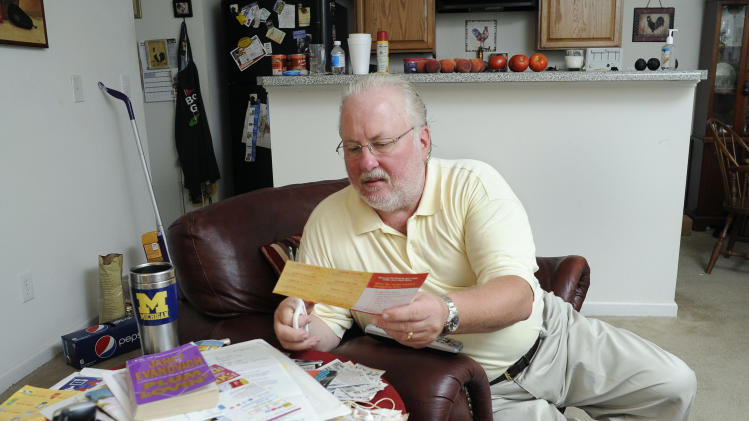 Greg Mann, an unemployed research analyst and real estate appraiser, sorts and cuts coupons at his home Tuesday, Aug. 14, 2012, in Braselton, Ga.. The recession that ended three years ago lingers on as the worst economic  recovery since the Great Depression. (AP Photo/John Amis)