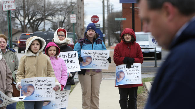 In this March 8, 2011 photo, anti-abortion protesters gather outside the Hope Clinic for Women in Granite City, Ill., as Rev. Chris Comerford, right, from St. Elizabeth's Catholic Church in Granite City speaks out against the abortion clinic. It's legal to get an abortion in America, but in many places it is hard and getting harder. Just this year, 17 states set new limits on abortion; 24 did last year, according to the Guttmacher Institute. Most states now require pre-abortion counseling, and over two dozen require waiting periods. In several of these states, the number of abortions has fallen, pleasing abortion opponents who say the laws are working. (AP Photo/The Telegraph, John Badman)