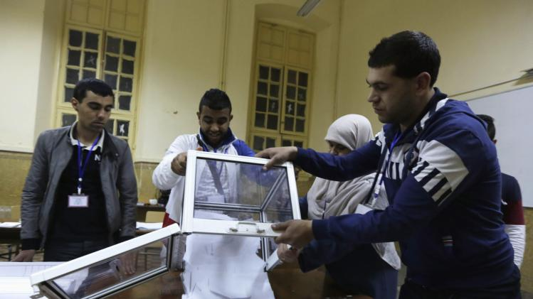 Election officials empty ballot box during vote counting process at polling station in Algiers