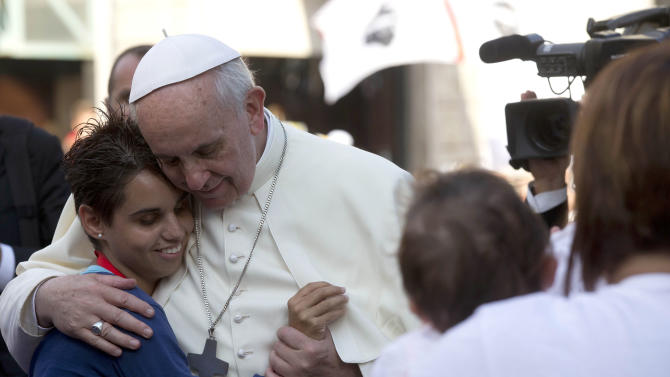 Pope Francis hugs a girl as he arrives for a meeting with youths in downtown Cagliari, Italy, Sunday, Sept. 22, 2013. Francis denounced what he called big business's idolatry of money over man as he traveled Sunday to one of Italy's poorest regions to offer hope to the unemployed and entrepreneurs struggling to hang on. (AP Photo/Alessandra Tarantino)