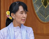 Myanmar opposition leader Aung San Suu Kyi gestures as she walks out of a hotel on her way to a meeting with President Thein Sein at the president's official residence in the capital Naypyidaw on April 11, 2012. Suu Kyi held talks with Thein Sein for the first time since her landmark election to political office earlier this month. AFP PHOTO / Soe Than WIN
