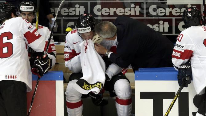 Switzerland's Helbling receives medical assistance after an injury during their Ice Hockey World Championship game against France at the O2 arena in Prague