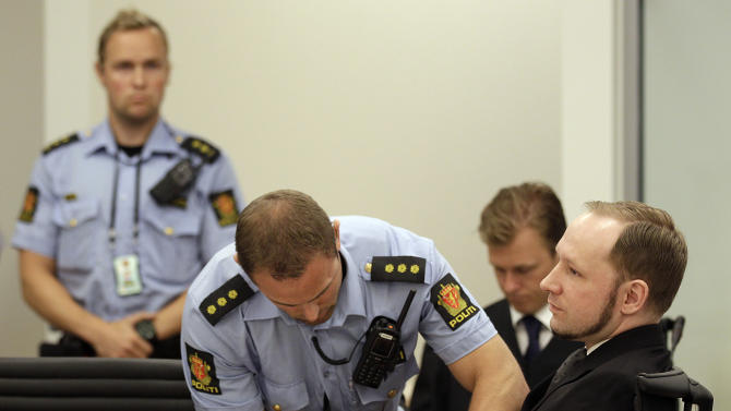 Mass murderer Anders Behring Breivik, right,  has his handcuffs released after he arrived at the court room in a courthouse in Oslo  Friday Aug. 24, 2012 . Breivik has been declared sane and sentenced to prison for bomb and gun attacks that killed 77 people last year. (AP Photo/Frank Augstein)