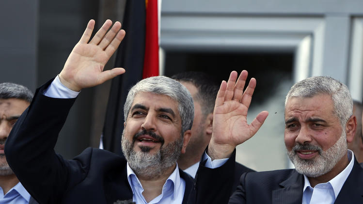 Exiled Hamas chief Khaled Mashaal, left, and Gaza's Hamas Prime Minister Ismail Haniyeh wave during a news conference upon Meshaal's arrival at Rafah crossing in the southern Gaza Strip, Friday, Dec. 7, 2012. Mashaal broke into tears Friday as he arrived in the Gaza Strip for his first-ever visit, a landmark trip reflecting his militant group's growing international acceptance and its defiance of Israel. Khaled Mashaal, who left the West Bank as a child and leads the Islamic militant movement from Qatar, crossed the Egyptian border, kissed the ground, and was greeted by a crowd of Hamas officials and representatives of Hamas' rival Fatah party. He was also welcomed by a group of Palestinian orphans — children of Gaza militants killed by Israel in recent years — wearing military-style uniforms. (AP Photo/Suhaib Salem, Pool)