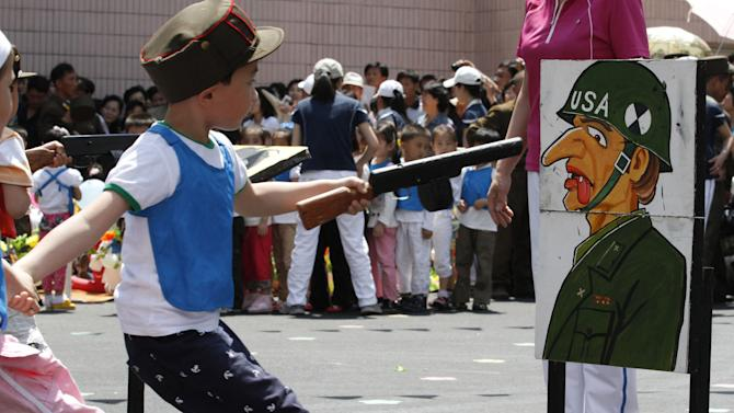 FILE - In this June 1, 2012 file photo, a child points a toy gun at a painting of a U.S. soldier during a game for children on the grounds of Kyongsang Kindergarten in Pyongyang, North Korea as the country marked International Children's Day.  For North Koreans, the systematic indoctrination of anti-Americanism starts as early as kindergarten and is as much a part of the curriculum as learning to count. (AP Photo/Kim Kwang Hyon, File)