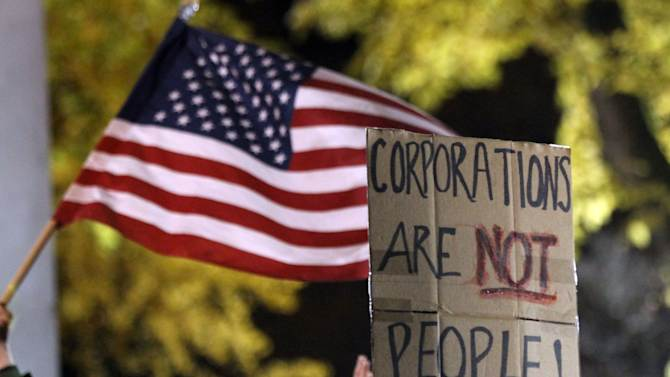 An American flag and sign are visible as hundreds gather hours before a mandate from the city to vacate the Occupy Portland Camp in Portland, Ore., Saturday, Nov. 12, 2011.(AP Photo/Don Ryan)
