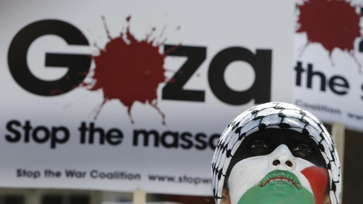 A demonstrator with face painted in the colours of the Palestinian flag protests outside the Israeli Embassy in west London