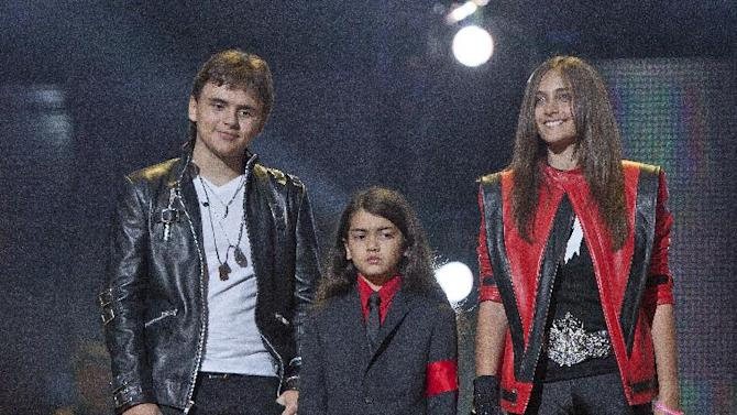 "FILE - In this Oct. 8, 2011 file photo, from left, Prince Jackson, Prince Michael II ""Blanket""Jackson and Paris Jackson arrive on stage at the Michael Forever the Tribute Concert, at the Millennium Stadium in Cardiff, Wales. Jurors hearing a civil case in Los Angeles filed by Jackson's mother, Katherine Jackson, have heard numerous stories about the entertainer's devotion to his children as expressed through extravagant birthday parties and secret family outings. The tender moments have been described throughout the trial, which concluded its eighth week on Friday, June 21, 2013. (AP Photo/Joel Ryan, file) *Editorial Use Only*"