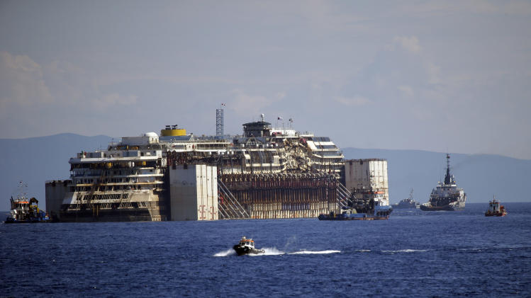 The Costa Concordia cruise wreck is towed away from the tiny Tuscan island of Isola del Giglio, Italy, Wednesday, July 23, 2014. After more than two years since it slammed into a reef along the coastline of Isola del Giglio the wreck has begun its last journey, to the Italian port of Genoa, where it will be scrapped. 32 people died in the incident. (AP Photo/Gregorio Borgia)