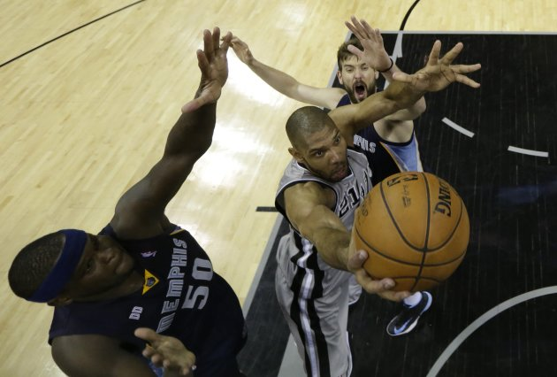Spurs forward Duncan goes up for the shot as he is defended by  Grizzlies forward Randolph and center Gasol during their NBA basketball game in San Antonio, Texas