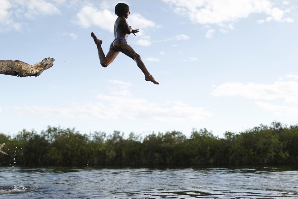 A Yawalapiti boy jumps into the Xingu River in the Xingu National Park