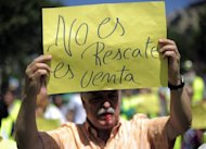 &lt;p&gt;An activist from the &#39;Yayoflautas&#39; movement holds a sign reading &#39;&#39;it is not a rescue, it is sale&quot; during a protest in Barcelona, on June 22. In recent months, bailouts for the banks -- whose risky real estate loans are blamed for inflating a housing bubble that burst in 2008, throwing millions out of work -- have sharpened protestors&#39; anger.&lt;/p&gt;