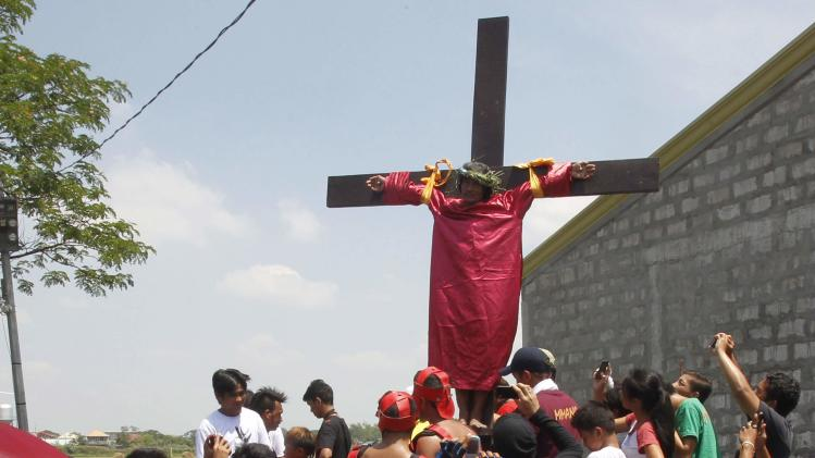 Jelico Jibe, 57, is watched by villagers as he is nailed to a wooden cross, to mark the death of Jesus Christ, on Good Friday in San Matias town, Pampanga province, north of Manila