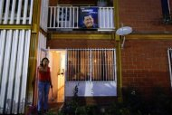 A woman stands outside her apartment next to a portrait of the late Venezuelan President Hugo Chavez in Ciudad Caribia outside Caracas September 26, 2013. REUTERS/Jorge Silva