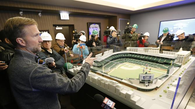 Crane Kenney, the Chicago Cubs' president of business operations, left, talks to the media about the progress and setbacks in the renovation of Wrigley Field as opening day approaches Monday, March 2, 2015, in Chicago. Chicago Cubs officials plan to ask the city for permission to work around the clock to speed up Wrigley Field renovations. (AP Photo/Charles Rex Arbogast)