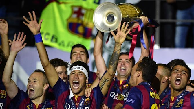 Barcelona's Andres Iniesta (L) and Neymar (C) celebrate with the trophy after winning the Champions League final against Juventus in Berlin on June 6, 2015