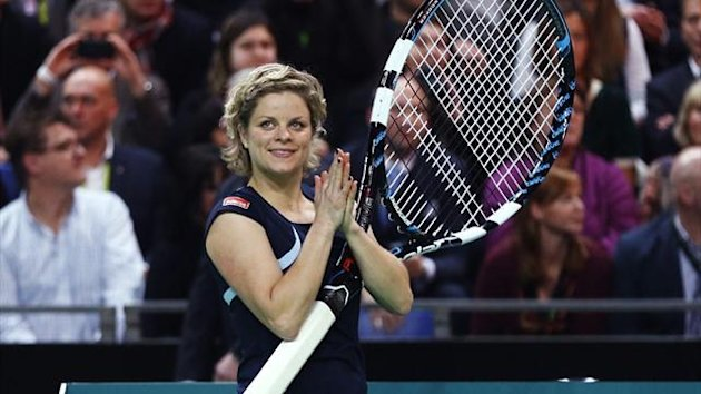 Kim Clijsters applauds after receiving a giant racquet during an exhibition tennis match against Venus Williams in Antwerp (Reuters)