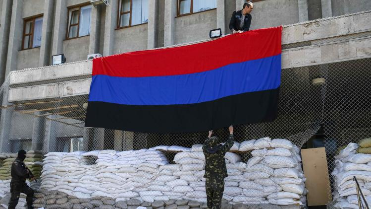 "Pro-Russian activists hang a giant flag of ""Donetsk Republic"" at the mayor's office in Slaviansk"