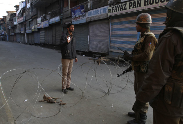 Indian paramilitary soldiers interrogate a civilian near a barbed wire set up as road blockade during curfew in Srinagar, India, Saturday, Feb. 9, 2013. A Kashmiri man Mohammed Afzal Guru, convicted i
