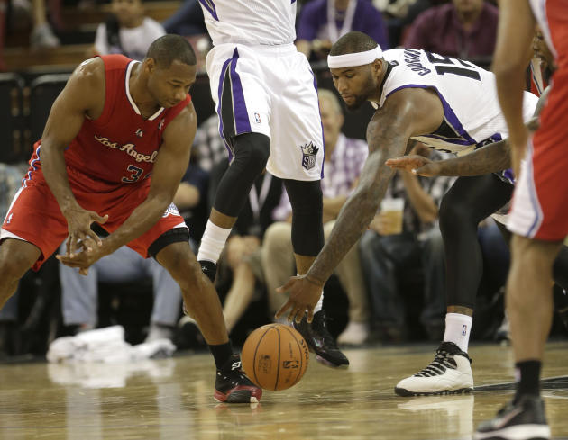 Sacramento Kings center DeMarcus Cousins, right, chases after the ball against Los Angeles Clippers guard Willie Green, left, during the third quarter of an NBA preseason basketball game in Sacramento