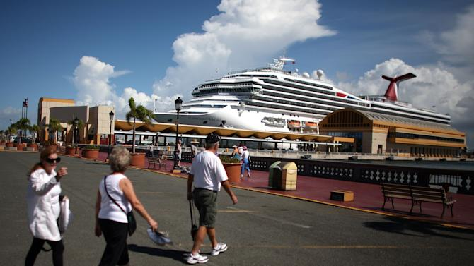 In this Oct. 2, 2012 photo, tourists walk through a parking lot in front of a pier where a cruise ship is docked in Old San Juan, Puerto Rico. Trade groups say the flourishing cruise ship industry injects about $2 billion a year into the economies of the Caribbean, the world's No. 1 cruise destination, but critics complain that it produces relatively little local revenue because so many passengers dine, shop and purchase heavily marked-up shore excursions on the boats or splurge at international chain shops on the piers.  (AP Photo/Ricardo Arduengo)