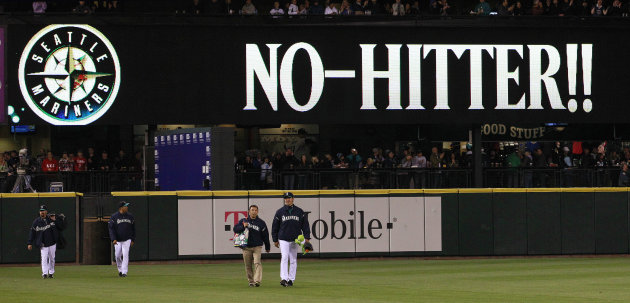 Seattle Mariners head in from the bullpen as a sign flashes &quot;No-Hitter!!&quot; behind after a baseball game against the Los Angeles Dodgers Friday, June 8, 2012, in Seattle. The Mariners won 1-0 in a six-p