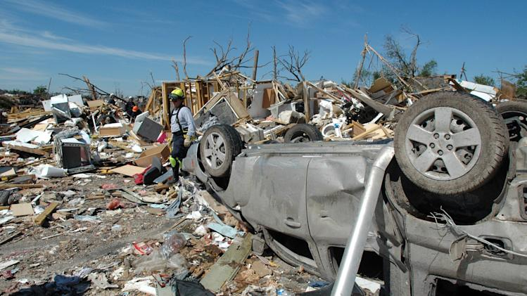 Louisiana Task Force 1 member Jesse Davis, center, continues to search a pile of rubble where cadaver dogs indicated a scent of human remains in the Alberta City community of Tuscaloosa, Ala., Thursday, May 5, 2011. Authorities continue the search for those missing.  (AP Photo/Jay Reeves)