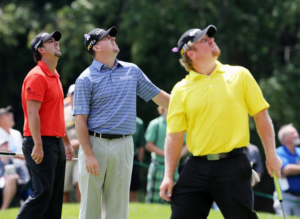 From left to right, leaders Scott Piercy, Robert Garrigus and William McGirt look up at a vintage Lancaster bomber aircraft flying past during the Canadian Open golf tournament at the Hamilton Golf and County Club in Hamilton, Ontario, Saturday, July 28, 2012. (AP Photo/The Canadian Press, Dave Chidley)