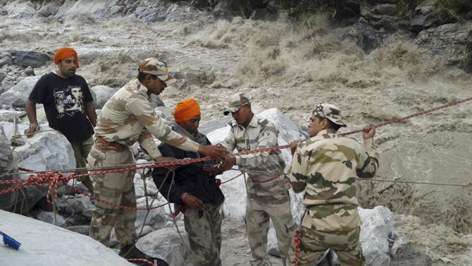 Indo-Tibetan Border Police (ITBP) use a rope to rescue stranded pilgrims, in saffron turban, cross a river swollen by flood waters at Ghangaria, in northern Indian state of Uttarakhand, India. Rescuers found 40 bodies floating in the River Ganges near a Hindu holy city on Friday, sending the death toll past 200 from flooding in northern India that has stranded tens of thousands of people, mostly Hindu pilgrims, since heavy monsoon rains began about a week ago. (AP Photo)