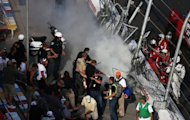 Track officials put out flames after a crash at the finish of the NASCAR Nationwide Series season-opener at Daytona International Speedway on February 23, 2013. The wreck began when Regan Smith turned sideways and a dozen cars bunched behind him