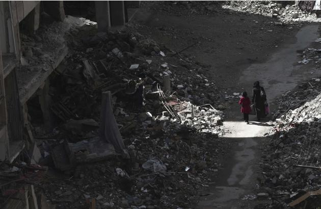 Civilians walk past rubble and damaged buildings in the Duma neighbourhood of Damascus