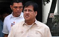 <p>Department of Interior and Local Government secretary Jesse Robredo (centre) leaves the Department of Justice building in Manila after a scheduled meeting with President Benigno Aquino in 2010. Robredo is among three people missing after a small plane crashed at sea off a central island on Saturday, officials said.</p>