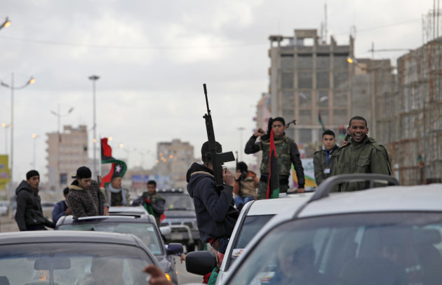 FILE - In this Sunday, Feb. 17, 2013 file photo, Libyan gunmen celebrate on the early morning of the second anniversary of the revolution that ousted Moammar Gadhafi, in Benghazi, Libya. More than 18 months since the end of Libya&#39;s civil war, the most attractive job for many of the young is still to join a militia. In fact, just under a tenth of Libya&#39;s labor force may be working as gunmen. State coffers are full of cash from rapidly reviving oil production, but rather than funding reconstruction, much of the money goes to buying off a restive population with state salaries, including to militias, effectively feeding a cycle of lawlessness. (AP Photo/Mohammad Hannon, File)