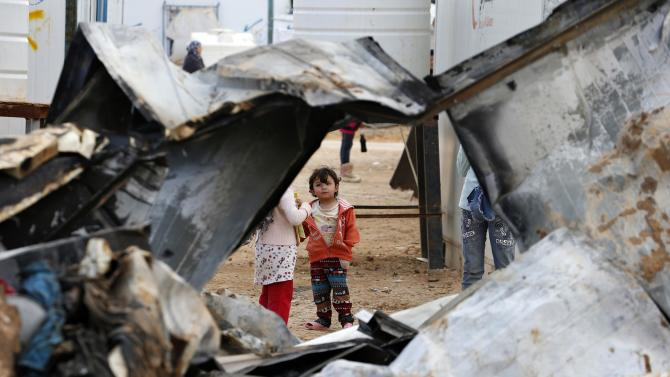 Syrian refugee children look at the remains of one of the caravans which was burnt at Al Zaatari