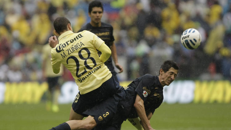 Pumas' Marco Antonio Palacios, right, heads the ball as he collides with America´s Martin Zuniga at a Mexican soccer league match in Mexico City, Saturday, Aug. 30, 2014. (AP Photo/Christian Palma)