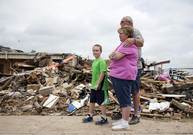 Julie Lewis watches with her husband Scott Lewis, and their son Zack, as President Barack Obama moves on with his tour of the devastation of Moore, Okla., after trying to comfort them Sunday, May 26,