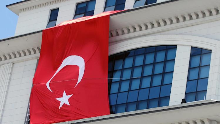A Turkish flag is hung from the headquarters of Turkish Prime Minister Recep Tayyip Erdogan's ruling party in Ankara, Turkey, Wednesday, March 20, 2013,  apparently to conceal the damage  after assailants fired a rocket on the building. Deputy Prime Minister Bulent Arinc, said the banned leftist group of Revolutionary People's Liberation Party-Front, or DHKP-C, that carried out a suicide bombing at the U.S. Embassy last month is believed to be behind simultaneous attacks on the party headquarters and the Justice Ministry parking lot.(AP Photo)