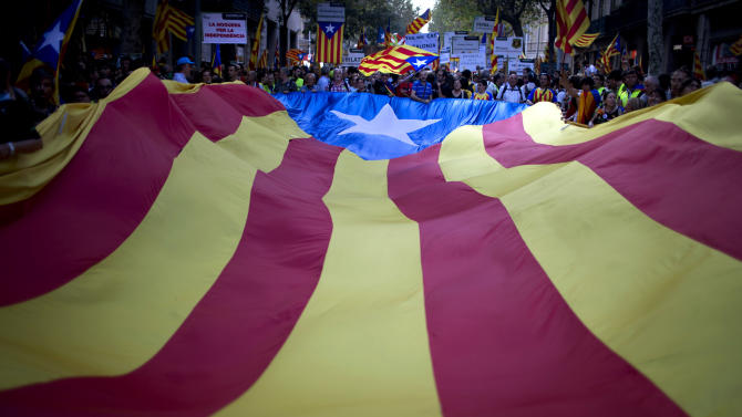 FILE - In this  Sept. 11, 2012 file photo, demonstrators carry a huge Catalan flag during a protest rally demanding independence for Catalonia in Barcelona, Spain. Spain raised €4.8 billion ($6.2 billion) in a debt auction Thursday Sept. 20, 2012 that saw strong demand and a drop in a benchmark interest rate, a sign that European plans to ease the debt crisis have helped investor confidence. Thursday's bond sale came as Catalonia regional government president Artur Mas met conservative Spanish Prime Minister Mariano Rajoy for talks on his demand for greater fiscal powers so that his powerful northeastern region can better manage its debt and deficit burdens. News reports had said that if denied extra fiscal powers Mas would call early regional elections that could turn into a referendum on independence and cause further problems for the central government. (AP Photo/Emilio Morenatti, File)
