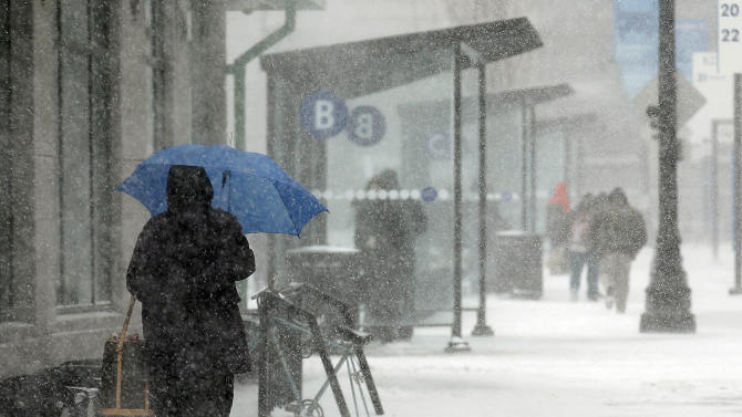 A passenger waits in the snow to board a bus at Kennedy Plaza in Providence, R.I., Monday, Feb. 8, 2016. Massachusetts, Rhode Island and eastern Connecticut, could see winter storm conditions with an accumulation of 4 to 8 inches. The heaviest snowfall is expected during Monday's morning commute through the afternoon. (AP Photo/Stew Milne)